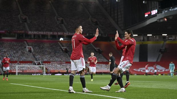 Manchester United's Mason Greenwood, left, celebrates with Edinson Cavani after scoring his side's first goal during the English FA Cup 4th round soccer match between Manchester United and Liverpool at Old Trafford in Manchester, England, Sunday, Jan. 24, 2021. (Laurence Griffiths/Pool via AP)