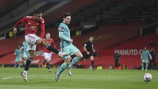 Manchester United's Mason Greenwood, left, scores his side's first goal during the English FA Cup 4th round soccer match between Manchester United and Liverpool at Old Trafford in Manchester, England, Sunday, Jan. 24, 2021. (Laurence Griffiths/Pool via AP)
