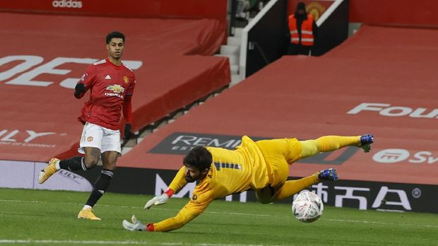 Manchester United's Marcus Rashford scores his sides second goal of the game past a diving Liverpool's goalkeeper Alisson during the English FA Cup 4th round soccer match between Manchester United and Liverpool at Old Trafford in Manchester, England, Sunday, Jan. 24, 2021. (Phil Noble/Pool via AP)