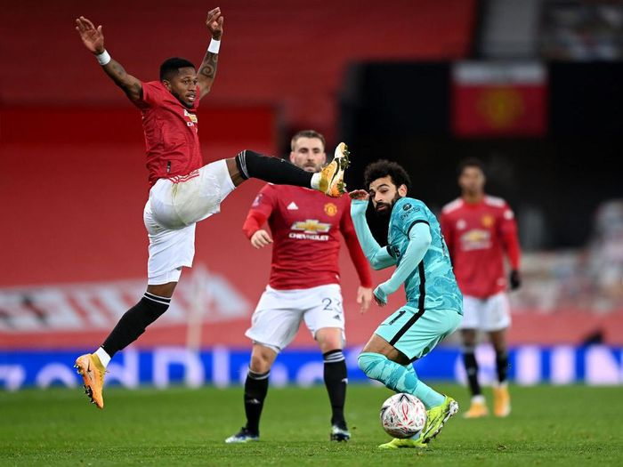 MANCHESTER, ENGLAND - JANUARY 24: Fred of Manchester United jumps for the ball as Mohamed Salah of Liverpool takes evasive action during The Emirates FA Cup 4th Round match between Manchester United and Liverpool at Old Trafford on January 24, 2021 in Manchester, England. Sporting stadiums around the UK remain under strict restrictions due to the Coronavirus Pandemic as Government social distancing laws prohibit fans inside venues resulting in games being played behind closed doors. (Photo by Laurence Griffiths/Getty Images)