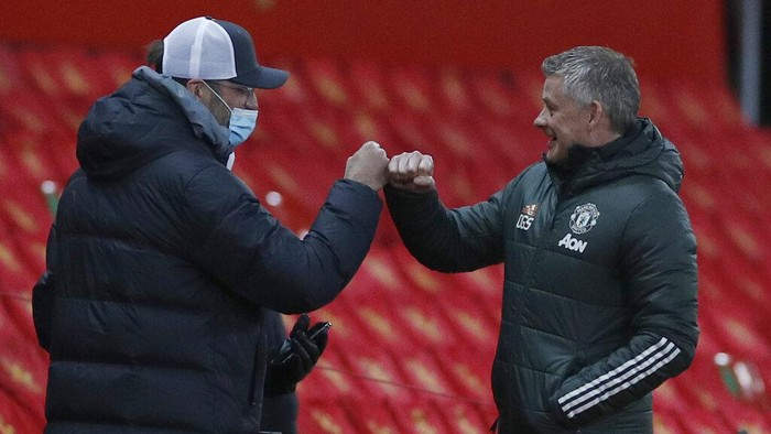 Liverpools manager Jurgen Klopp, left and Manchester Uniteds manager Ole Gunnar Solskjaer bumps fists just prior to kick off for the English FA Cup 4th round soccer match between Manchester United and Liverpool at Old Trafford in Manchester, England, Sunday, Jan. 24, 2021. (Phil Noble/Pool via AP)