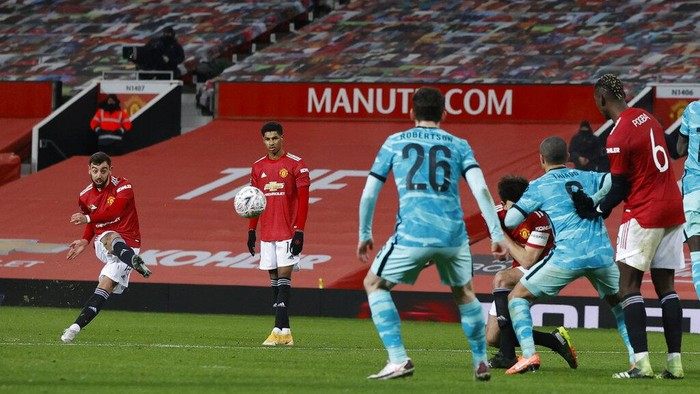Manchester Uniteds Bruno Fernandes, left shoots and scores from a free kick his sides 3rd goal of the game during the English FA Cup 4th round soccer match between Manchester United and Liverpool at Old Trafford in Manchester, England, Sunday, Jan. 24, 2021. (Phil Noble/Pool via AP)