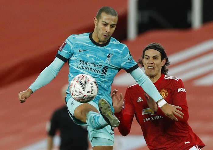 Liverpools Thiago, attempts to control the ball under pressure from Manchester Uniteds Edinson Cavani during the English FA Cup 4th round soccer match between Manchester United and Liverpool at Old Trafford in Manchester, England, Sunday, Jan. 24, 2021. (Phil Noble/Pool via AP)