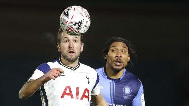 Tottenham's Harry Kane, left, and Wycombe's Darius Charles challenge for the ball during the English FA Cup 4th round soccer match between Wycombe Wanderers and Tottenham Hotspur at Adams Park stadium in High Wycombe, England, Monday, Jan. 25, 2021. (AP Photo/Frank Augstein)
