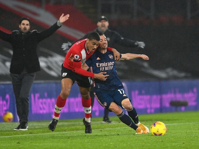 SOUTHAMPTON, ENGLAND - JANUARY 26: Yan Valery of Southampton is challenged by Cedric Soares of Arsenal as Mikel Arteta, Manager of Arsenal and Ralph Hasenhuttl, Manager of Southampton react during the Premier League match between Southampton and Arsenal at St Marys Stadium on January 26, 2021 in Southampton, England. Sporting stadiums around the UK remain under strict restrictions due to the Coronavirus Pandemic as Government social distancing laws prohibit fans inside venues resulting in games being played behind closed doors. (Photo by Andy Rain - Pool/Getty Images)