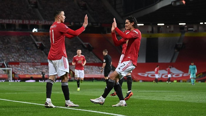 MANCHESTER, ENGLAND - JANUARY 24: Mason Greenwood of Manchester United celebrates after scoring their sides first goal  with team mate Edinson Cavani during The Emirates FA Cup Fourth Round match between Manchester United and Liverpool at Old Trafford on January 24, 2021 in Manchester, England. Sporting stadiums around the UK remain under strict restrictions due to the Coronavirus Pandemic as Government social distancing laws prohibit fans inside venues resulting in games being played behind closed doors. (Photo by Laurence Griffiths/Getty Images)