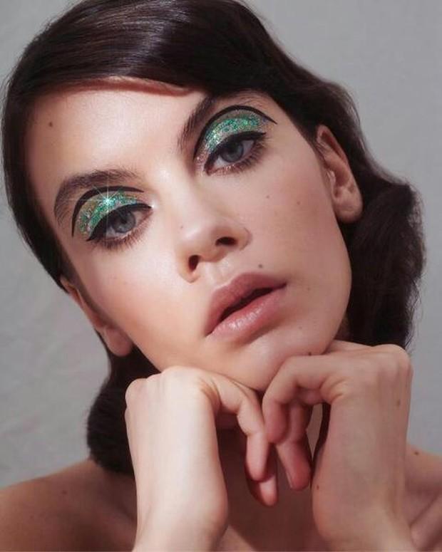 Emerald lids dengan aksen eyeliner hitam menciptakan getaran tahun 1960-an.
