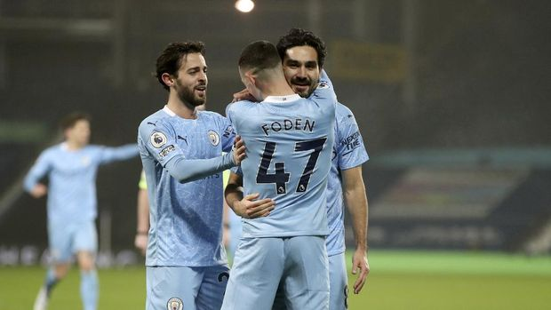 Manchester City's Ilkay Gundogan, right, celebrates with teammates after scoring his side's third goal during the English Premier League soccer match between West Bromwich Albion and Manchester City at the Hawthorns stadium in West Bromwich, England, Tuesday, Jan. 26, 2021. (Nick Potts/Pool via AP)