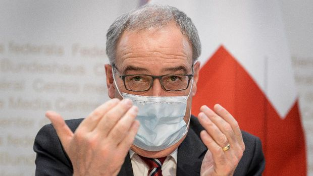 Swiss President Guy Parmelin (L) gives a press conference on new measures to control the spread of the Covid-19 pandemic caused by the novel coronavirus, on January 13, 2021 in Bern. (Photo by Fabrice COFFRINI / AFP)