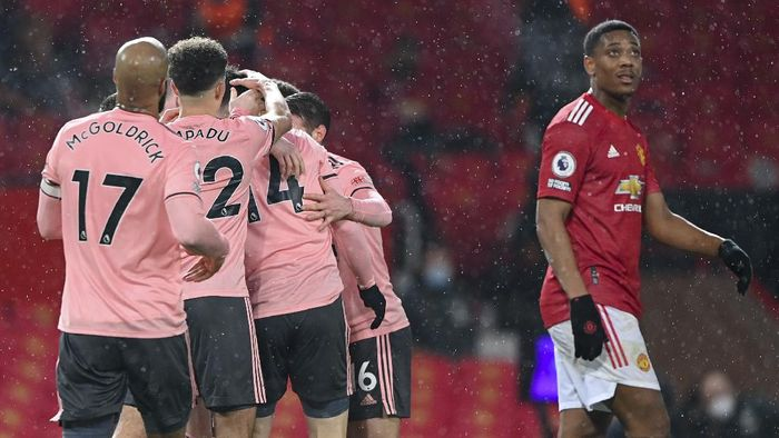 Sheffield Uniteds Oliver Burke, is congratulated by teammates after scoring his teams second goal during the English Premier League soccer match between Manchester United and Sheffield United at Old Trafford, Manchester, England, Wednesday, Jan. 27, 2021. (AP Photo/Laurence Griffiths,Pool)