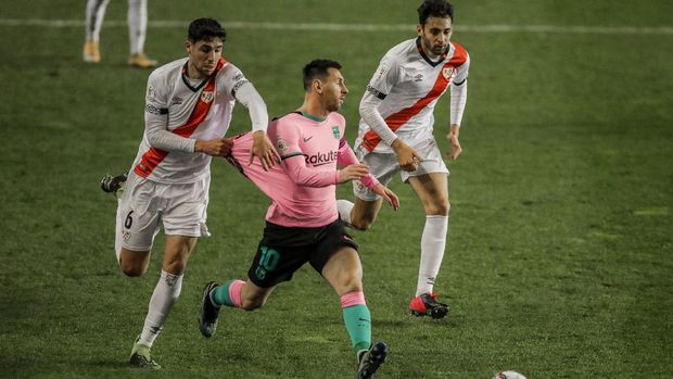 Barcelona's Lionel Messi, center, and Rayo's Santiago Comensano, left, during a Spanish Copa del Rey round of 16 soccer match between Rayo Vallecano and FC Barcelona at the Vallecas stadium in Madrid, Spain, Wednesday, Jan. 27, 2021. (AP Photo/Manu Fernandez)