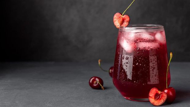 Cold cherry juice with ice on a dark background. Copy space