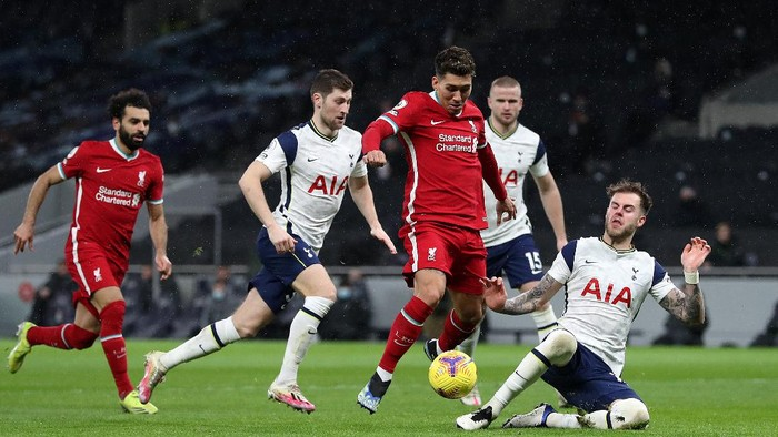 LONDON, ENGLAND - JANUARY 28: Roberto Firmino of Liverpool is tackled by Joe Rodon of Tottenham Hotspur during the Premier League match between Tottenham Hotspur and Liverpool at Tottenham Hotspur Stadium on January 28, 2021 in London, England. Sporting stadiums around the UK remain under strict restrictions due to the Coronavirus Pandemic as Government social distancing laws prohibit fans inside venues resulting in games being played behind closed doors. (Photo by Catherine Ivill/Getty Images)