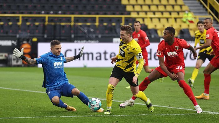 DORTMUND, GERMANY - JANUARY 30: Marco Reus of Borussia Dortmund is put under pressure by Rafal Gikiewicz (L) and Reece Oxford (R) of Augsburg during the Bundesliga match between Borussia Dortmund and FC Augsburg at Signal Iduna Park on January 30, 2021 in Dortmund, Germany. Sporting stadiums around Germany remain under strict restrictions due to the Coronavirus Pandemic as Government social distancing laws prohibit fans inside venues resulting in games being played behind closed doors. (Photo by Lars Baron/Getty Images)