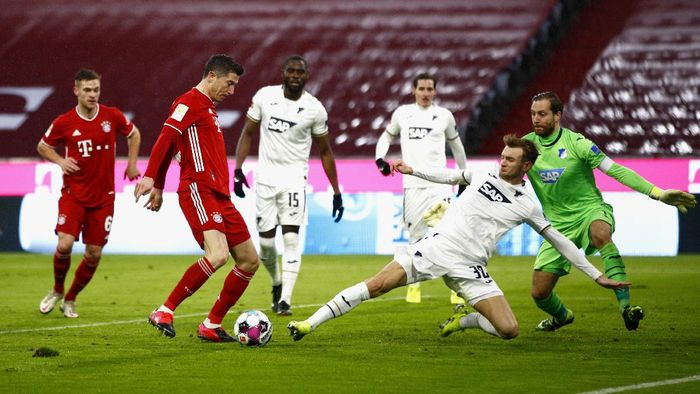 MUNICH, GERMANY - JANUARY 30: Robert Lewandowski of FC Bayern Munich scores his teams third goal past Oliver Baumann of TSG 1899 Hoffenheim during the Bundesliga match between FC Bayern Muenchen and TSG Hoffenheim at Allianz Arena on January 30, 2021 in Munich, Germany. Sporting stadiums around Germany remain under strict restrictions due to the Coronavirus Pandemic as Government social distancing laws prohibit fans inside venues resulting in games being played behind closed doors. (Photo by Adam Pretty/Getty Images)