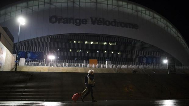 A woman walks by the velodrome stadium in Marseille, southern France, Saturday Jan. 30, 2021.The French league postponed Marseille's home game against Rennes just three hours before kickoff on Saturday after angry Marseille fans marched to the club's training complex to protest poor results. (AP Photo/Daniel Cole)