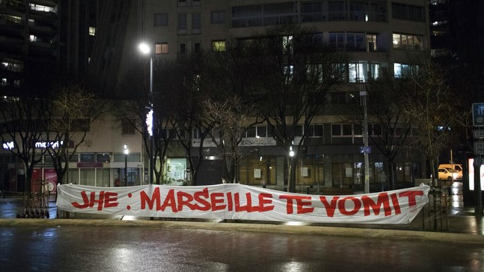 A woman walks by the velodrome stadium in Marseille, southern France, Saturday Jan. 30, 2021.The French league postponed Marseilles home game against Rennes just three hours before kickoff on Saturday after angry Marseille fans marched to the clubs training complex to protest poor results. (AP Photo/Daniel Cole)