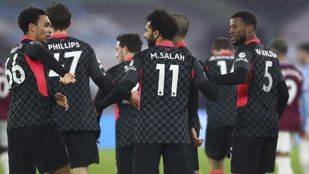 Liverpool's Mohamed Salah, center, celebrates after scoring his side's opening goal during the English Premier League match between West Ham and Liverpool at the the London Stadium in London, Sunday, Jan. 31, 2021. (Clive Rose/Pool via AP)