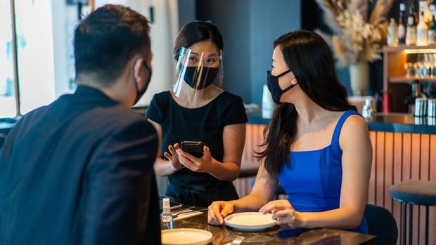 Asian waitress with face mask and face shield taking food orders from customers.
