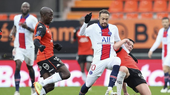 PSGs Neymar, center, challenges for the ball with Lorients Yoane Wissa, left, and Laurent Abergel, right, during the French League One soccer match between FC Lorient and Paris Saint-Germain at the Moustoir stadium in Lorient, western France, Sunday, Jan. 31, 2021. (AP Photo/David Vincent)