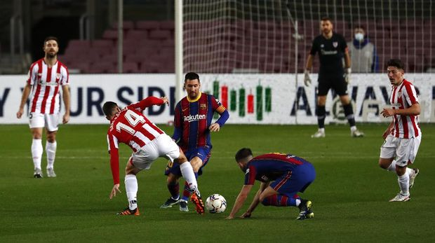 Barcelona's Lionel Messi, center, fights for the ball with Athletic Bilbao's Dani Garcia during the Spanish La Liga soccer match between FC Barcelona and Athletic Bilbao at the Camp Nou stadium in Barcelona, Spain, Sunday, Jan. 31, 2021. (AP Photo/Joan Monfort)