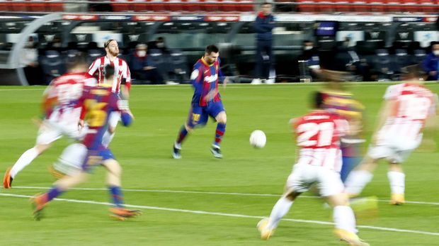 In this photo taken with slow shutter speed, Barcelona's Lionel Messi, center, runs with the ball during the Spanish La Liga soccer match between FC Barcelona and Athletic Bilbao at the Camp Nou stadium in Barcelona, Spain, Sunday, Jan. 31, 2021. (AP Photo/Joan Monfort)
