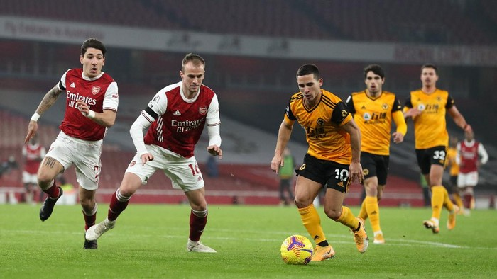 LONDON, ENGLAND - NOVEMBER 29: Daniel Podence of Wolverhampton Wanderers beats Hector Bellerin and Rob Holding of Arsenal during the Premier League match between Arsenal and Wolverhampton Wanderers at Emirates Stadium on November 29, 2020 in London, England. Sporting stadiums around the UK remain under strict restrictions due to the Coronavirus Pandemic as Government social distancing laws prohibit fans inside venues resulting in games being played behind closed doors. (Photo by Catherine Ivill/Getty Images)