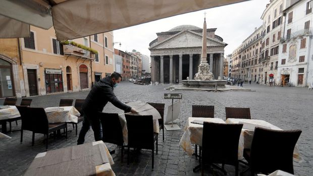 A cafe employee prepares tables near the Pantheon after the coronavirus disease (COVID-19) restrictions were eased in Lazio region, Rome, Italy, February 1, 2021. REUTERS/Yara Nardi