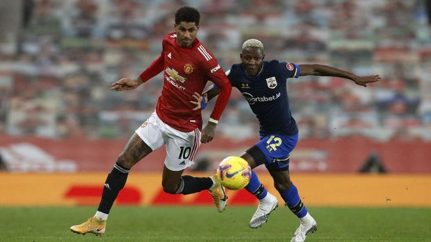 Manchester United's Marcus Rashford, left, duels for the ball with Southampton's Moussa Djenepo during the English Premier League soccer match between Manchester United and Southampton, at the Old Trafford stadium in Manchester, England, Tuesday, Feb. 2, 2021. (Phil Noble/Pool via AP)