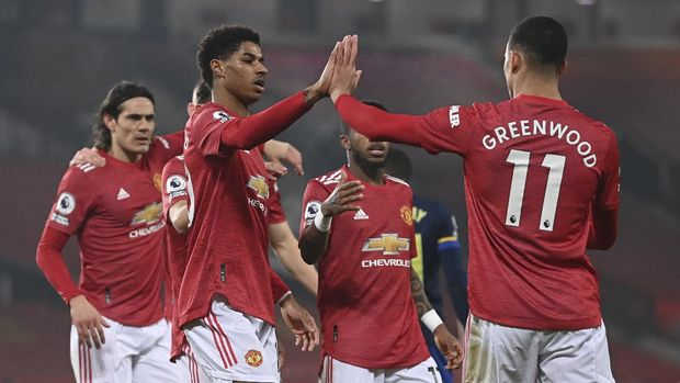 Manchester United's Marcus Rashford, front left, celebrates with teammates after scoring his side's second goal during the English Premier League soccer match between Manchester United and Southampton, at the Old Trafford stadium in Manchester, England, Tuesday, Feb. 2, 2021. (Laurence Griffiths/Pool via AP)