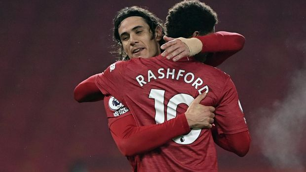 Manchester United's Edinson Cavani, left, celebrates with Manchester United's Marcus Rashford after scoring his side's fourth goal during English Premier League soccer match between Manchester United and Southampton, at the Old Trafford stadium in Manchester, England, Tuesday, Feb. 2, 2021. (Laurence Griffiths/Pool via AP)