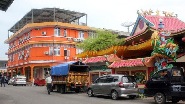 Singkawang, West Kalimantan, Indonesia  - August 29, 2013:  Confucian temple and traffic on the road of the Singkawang city, West Kalimantan, Indonesia.