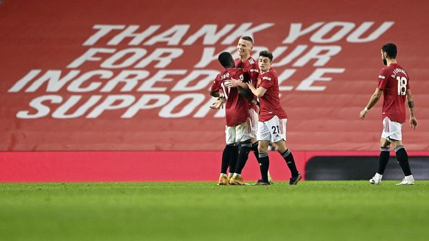Manchester United's Scott McTominay celebrates with teammates after scoring his side's sixth goal during the English Premier League soccer match between Manchester United and Southampton, at the Old Trafford stadium in Manchester, England, Tuesday, Feb. 2, 2021. (Laurence Griffiths/Pool via AP)
