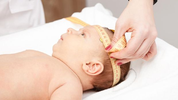 Close-up shot of pediatrician examines two months baby boy. Doctor using measurement tape checking baby head size