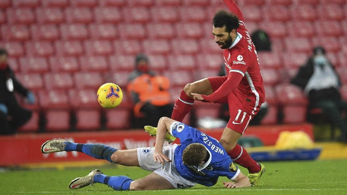 Liverpools Mohamed Salah, right, is tackled by Brightons Adam Webster during the English Premier League soccer match between Liverpool and Brighton at Anfield stadium, in Liverpool, England, Wednesday, Feb. 3, 2021. (Paul Ellis/Pool via AP)