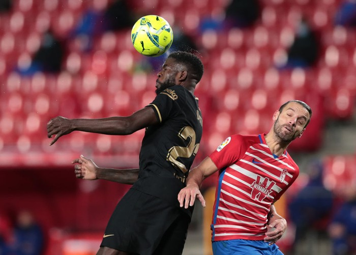 GRANADA, SPAIN - JANUARY 09: Samuel Umtiti of Barcelona wins a header over Roberto Soldado of Granada during the La Liga Santander match between Granada CF and FC Barcelona at Estadio Nuevo Los Carmenes on January 09, 2021 in Granada, Spain. Sporting stadiums around Spain remain under strict restrictions due to the Coronavirus Pandemic as Government social distancing laws prohibit fans inside venues resulting in games being played behind closed doors. (Photo by Gonzalo Arroyo Moreno/Getty Images)