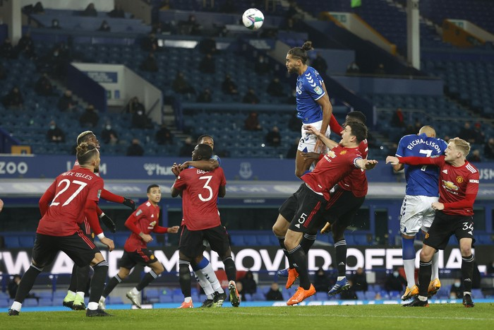LIVERPOOL, ENGLAND - DECEMBER 23: Dominic Calvert-Lewin of Everton wins a header under pressure from Harry Maguire and Axel Tuanzebe of Manchester United during the Carabao Cup Quarter Final match between Everton and Manchester United at Goodison Park on December 23, 2020 in Liverpool, England.  A limited number of fans (2000) are welcomed back to stadiums to watch elite football across England. This was following easing of restrictions on spectators in tiers one and two areas only. (Photo by Clive Brunskill/Getty Images)