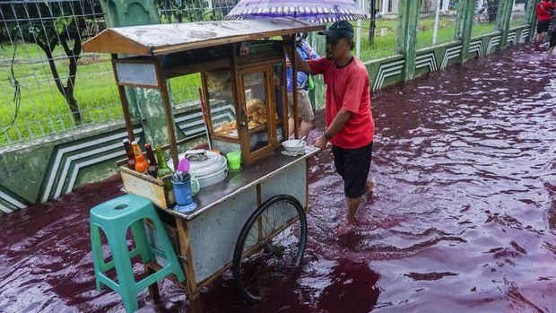 Pedagang bakso berjalan di jalan perkampungan yang tergenang banjir berwarna merah di Jenggot, Pekalongan, Jawa Tengah, Sabtu (6/2/2021). Menurut warga setempat, air banjir berwarna merah itu disebabkan oleh pencemaran limbah pewarna batik berwarna merah karena di lokasi tersebut terdapat ratusan pelaku usaha batik. ANTARA FOTO/Harviyan Perdana Putra/foc.