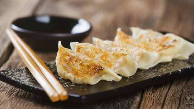 A plate of authentic Japanese gyoza potsticker appetizers with dipping sauce and chopsticks, against a wooden background.