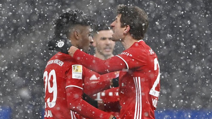 Bayerns Kingsley Coman, left, celebrates after scoring his sides opening goal during the German Bundesliga soccer match between Hertha BSC Berlin and FC Bayern Munich in Berlin, Germany, Friday, Feb. 5, 2021. (John MacDougall/pool via AP)