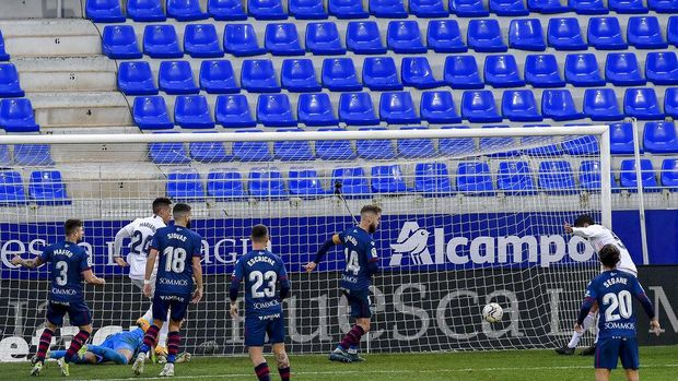 Real Madrid's Raphael Varane, right, scores his side's second goal during the Spanish La Liga soccer match between Huesca and Real Madrid at El Alcoraz stadium in Huesca, Spain, Saturday, Feb. 6, 2021. (AP Photo/Alvaro Barrientos)