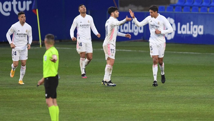 HUESCA, SPAIN - FEBRUARY 06: Raphael Varane of Real Madrid celebrates with team mate Marco Asensio after scoring their sides  first goal during the La Liga Santander match between SD Huesca and Real Madrid at Estadio El Alcoraz on February 06, 2021 in Huesca, Spain. Sporting stadiums around Spain remain under strict restrictions due to the Coronavirus Pandemic as Government social distancing laws prohibit fans inside venues resulting in games being played behind closed doors. (Photo by Alex Caparros/Getty Images)