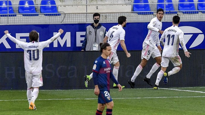 Real Madrids Raphael Varane, right, celebrates after scoring his sides second goal during the Spanish La Liga soccer match between Huesca and Real Madrid at El Alcoraz stadium in Huesca, Spain, Saturday, Feb. 6, 2021. (AP Photo/Alvaro Barrientos)