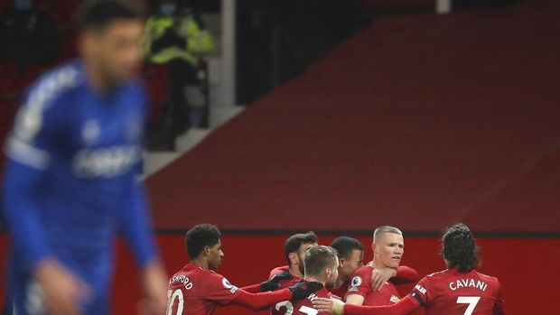 Manchester United's Scott McTominay, 2nd right, celebrates with team mates after scoring his side's third goal during an English Premier League soccer match between Manchester United and Everton at the Old Trafford stadium in Manchester, England, Saturday Feb. 6, 2021. (Martin Rickett/Pool via AP)