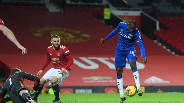 MANCHESTER, ENGLAND - FEBRUARY 06: Abdoulaye Doucoure of Everton scores their team's first goal past David De Gea and Luke Shaw of Manchester United during the Premier League match between Manchester United and Everton at Old Trafford on February 06, 2021 in Manchester, England. Sporting stadiums around the UK remain under strict restrictions due to the Coronavirus Pandemic as Government social distancing laws prohibit fans inside venues resulting in games being played behind closed doors. (Photo by Michael Regan/Getty Images)