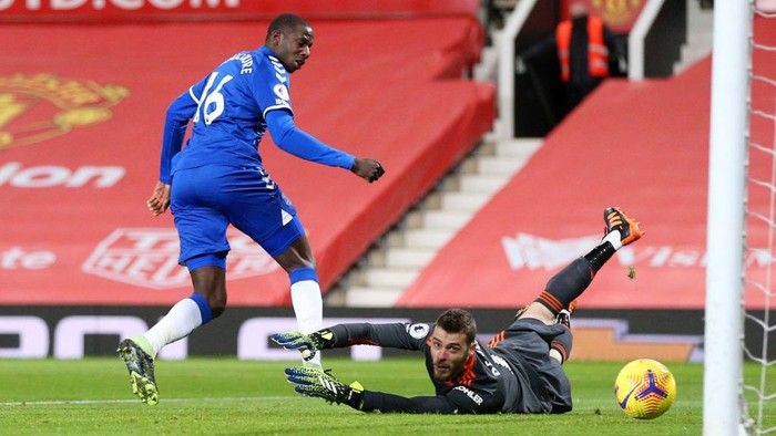 MANCHESTER, ENGLAND - FEBRUARY 06: Abdoulaye Doucoure of Everton scores their teams first goal past David De Gea of Manchester United during the Premier League match between Manchester United and Everton at Old Trafford on February 06, 2021 in Manchester, England. Sporting stadiums around the UK remain under strict restrictions due to the Coronavirus Pandemic as Government social distancing laws prohibit fans inside venues resulting in games being played behind closed doors. (Photo by Alex Pantling/Getty Images)