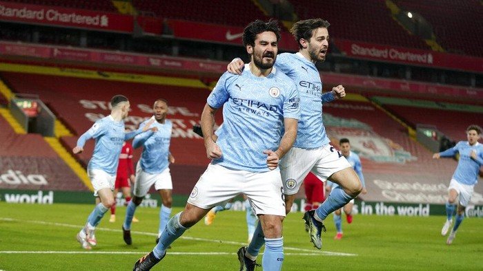 Manchester Citys Ilkay Gundogan celebrates with Bernardo Silva, center right, after scoring the opening goal during the English Premier League soccer match between Liverpool and Manchester City at Anfield Stadium, Liverpool, England, Sunday, Feb. 7, 2021. (AP photo/Jon Super, Pool)