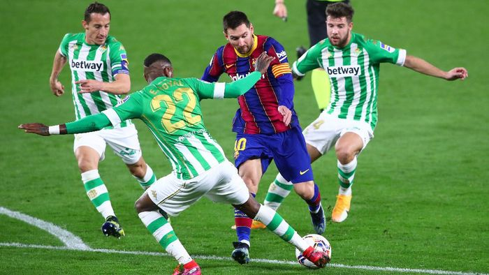 SEVILLE, SPAIN - FEBRUARY 07: Lionel Messi of FC Barcelona is challenged by Andres Guardado, Emerson Royal and Aitor Ruibal of Real Betis during the La Liga Santander match between Real Betis and FC Barcelona at Estadio Benito Villamarin on February 07, 2021 in Seville, Spain. Sporting stadiums around Spain remain under strict restrictions due to the Coronavirus Pandemic as Government social distancing laws prohibit fans inside venues resulting in games being played behind closed doors. (Photo by Fran Santiago/Getty Images)