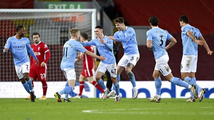 Manchester Citys Phil Foden, center, celebrates after scoring his sides fourth goal during the English Premier League soccer match between Liverpool and Manchester City at Anfield Stadium, Liverpool, England, Sunday, Feb. 7, 2021. (Laurence Griffiths/Pool via AP)