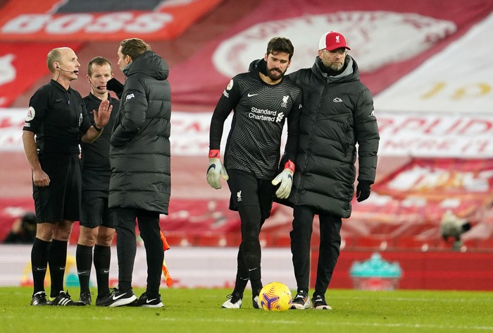 LIVERPOOL, ENGLAND - JANUARY 21: Pepijn Lijnders, assistant manager of Liverpool speaks with match referee, Mike Dean as Jurgen Klopp, Manager of Liverpool walks away with Alisson Becker of Liverpool after talking to match referee, Mike Dean and his officials following the Premier League match between Liverpool and Burnley at Anfield on January 21, 2021 in Liverpool, England. Sporting stadiums around the UK remain under strict restrictions due to the Coronavirus Pandemic as Government social distancing laws prohibit fans inside venues resulting in games being played behind closed doors. (Photo by Jon Super - Pool/Getty Images)
